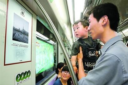 """昨天,""""解放号""""文化列车上,乘客饶有兴致地欣赏老照片。 蒋迪雯 摄"""