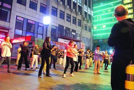 □在地铁10号线四平路站3号出口,每晚都有附近居民在空地上跳舞,妨碍了乘客出行。/晨报记者 殷立勤