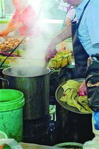 """□摊贩边用木棒搅拌煮鳝丝的铁桶边不时加""""料"""" 本版图片/晨报记者 陈征"""