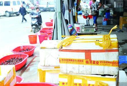 □在盱眙当地最大的小龙虾交易市场内,不少装运小龙虾的箱子封箱带上写着外地市场的名字。  本版图片/晨报记者 何雯亚