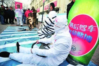 12月2日,济南交通安全宣传志愿者通过行为艺术表演,向路人宣传酒后驾车的危险性。新华社图片