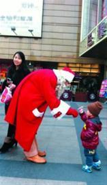 □巴黎春天门口,一个小男孩接过圣诞老人给他的棒棒糖。晨报记者 李宝花 现场图片
