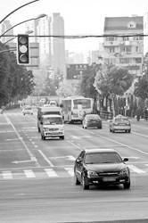 """昨天,在花园路中山北一路路口西向东方向,半小时内有十几辆车""""踏""""着黄灯过。本报记者 陈龙摄"""