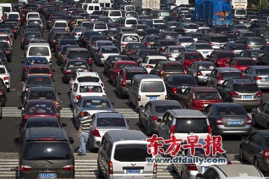 2012年9月30日,G2京沪高速上海安亭收费站北侧,大量车辆积压,一名男士倚靠着轿车。早报记者 杨深来 图