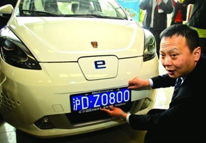 昨天,上海首张新能源汽车免费车牌亮相,车主钱先生亲手挂上新能源车专属牌照。/晨报记者 竺钢