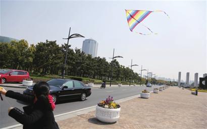 上海科技馆外的世纪广场上,放风筝者众多,沿路行人车辆川流不息。 □朱晓立 摄