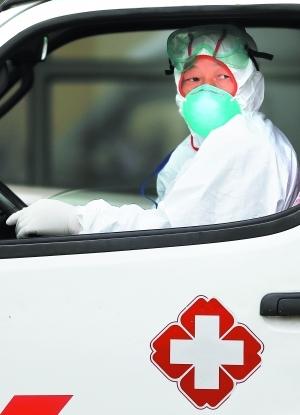 4月18日,上海市公共卫生中心内,一名穿着全套防护服的医护工作人员坐在救急车内,随时准备执行H7N9禽流感病人的运送任务。早报记者 杨一 图