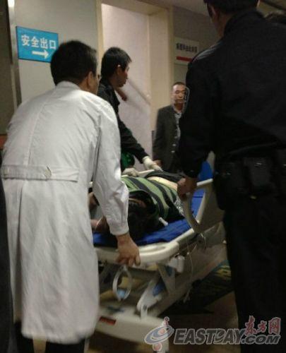 抢劫车辆的嫌疑人被拷上手铐,送医救治。