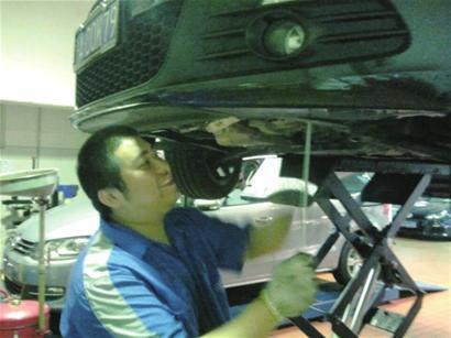 维修人员拆卸轿车底盘救猫