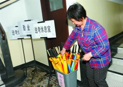 昨天,在上海一高考考点内,一名老师正在整理爱心伞。 本报记者 张驰 摄
