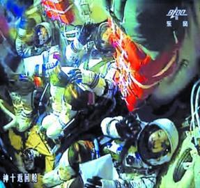 北京航天飞控中心的大屏幕图像显示了航天员在舱内的情况。 新华社发