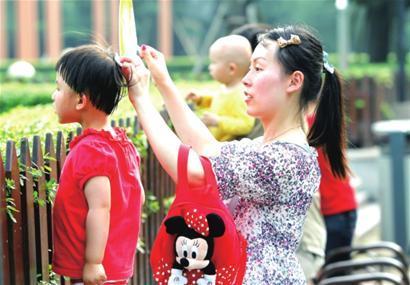 昨日高温,一位妈妈给孩子擦汗摇扇。□解放日报 陈 骏 摄