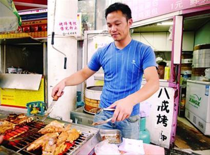 赖章平正在烤猪蹄。 岳诚 摄