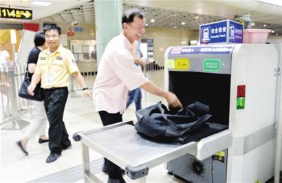 昨日在地铁2号线南京东路站,一名快递员正在配合安检。 □新闻晨报 肖 允 摄