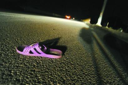 昨晚事发后,一只紫色塑料拖鞋孤零零躺在浦东、奉贤交界处的新四平公路上,而拖鞋的主人永远去了 晚报 何雯亚 现场图片
