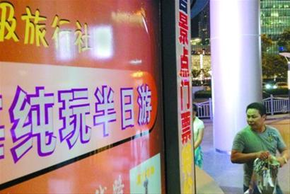 游客在旅行社前看旅游信息 晚报 王浩然现场图片