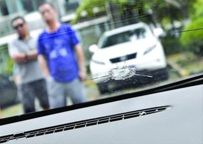 """遭到""""射击""""的车窗留下明显的弹孔,四周呈蛛网状碎裂。 晨报记者 肖允"""