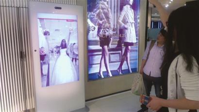 """昨日,一名女顾客在商场体验""""3D试衣镜""""。 □本报记者 陈 鑫 摄"""