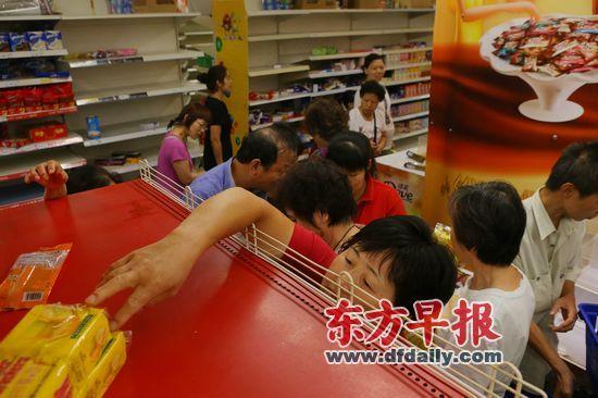 昨日,乐购长宁店,一名女士伸手拿货架上仅存的几包饼干。早报记者 王辰 图