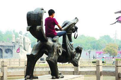 上海外滩,一名游客爬上雕塑。 晨报记者 杨眉