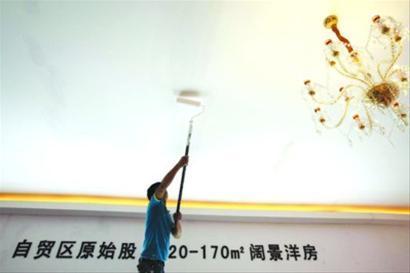 """工作人员争分夺秒布展,""""自贸区房""""概念现身一些展台。 晨报记者 杨眉"""