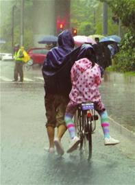 昨晨风雨中,市民艰难护送孩子上学。
