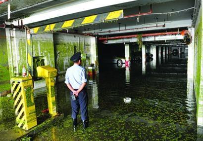 昨天,一名在现场执勤的警察正在查看即将抽干的地下车库。 本报记者 张驰 摄