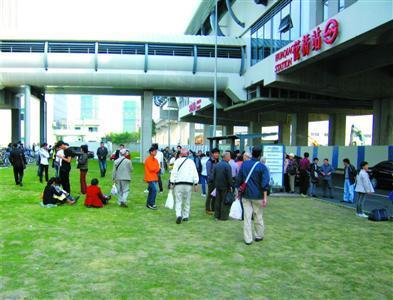 从轨交花桥站出来的乘客在草地上等候公交车。 本报记者 张家琳 摄