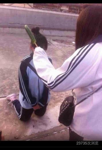 网上流传的照片显示,一名女生拿着黄瓜正教训跪在地上的女生。