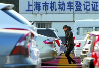 昨天,一位办理上牌手续的市民从上海市交警总队车辆管理所三分所的停车场经过。 新华社记者 裴鑫 摄