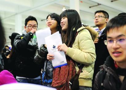 求职的大学生在现场了解招聘信息/张驰