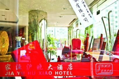 酒店大门用桌椅封堵,门口贴着写有某服装公司的封条 晨报记者/肖允