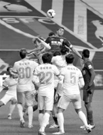 莫雷诺(上)在绿城球员包围中争抢头球 /晨报记者 顾力华