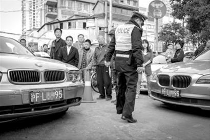 昨天下午,一交警在昆明路巡逻时发现两辆外形极为相似的宝马车,车牌竟完全一样。/晨报记者 肖允